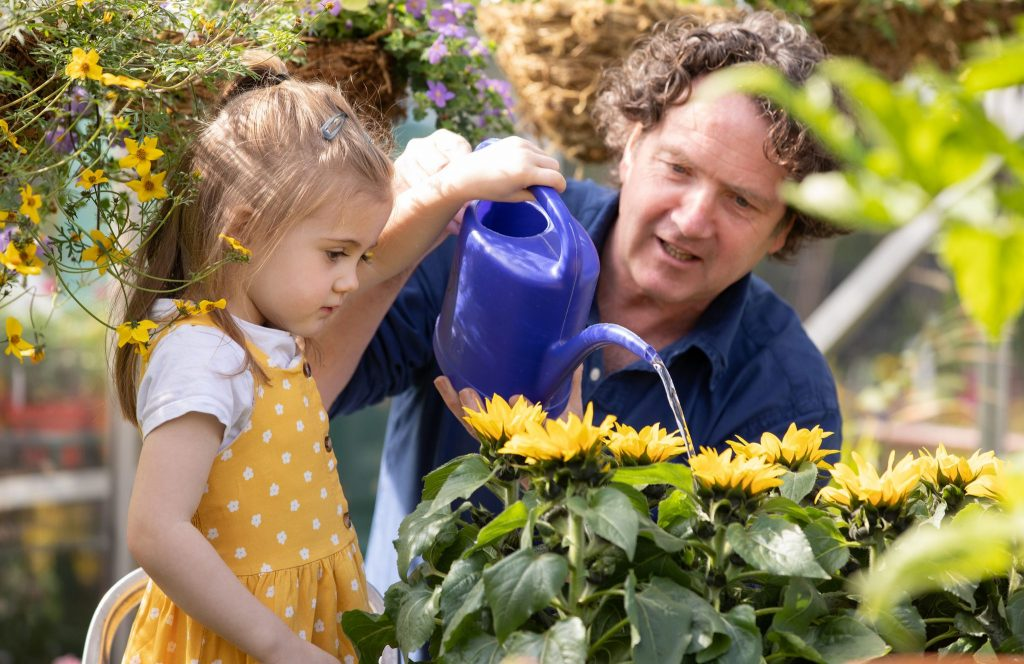 Diarmuid Gavin & little girl in yellow dress pouring water on sunflowers.   HOSPICE SUNFLOWER DAYS 2019 Launch PR photocall