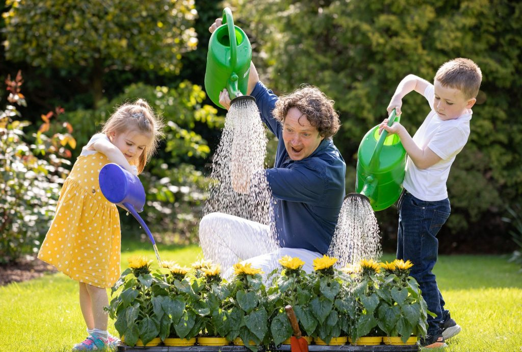 Diarmuid Gavin & little girl in yellow dress & little boy pouring water on sunflowers  PR Photographer Dublin:  HOSPICE SUNFLOWER DAYS 2019 Launch Photocall