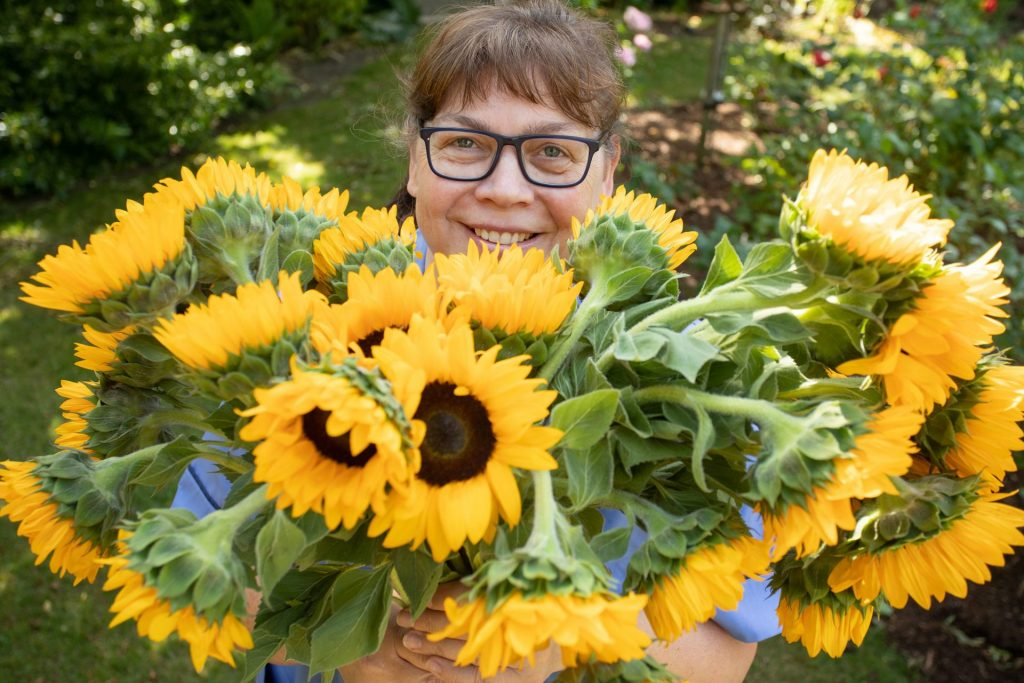 Nurse wearing glasses holding large bunch of sunflowers Press & PR Photography