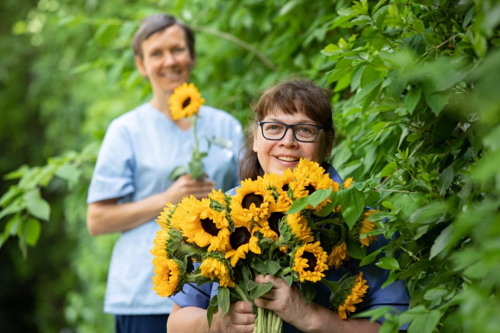 Two nurses from our ladys hospice holding sunflowers in garden area