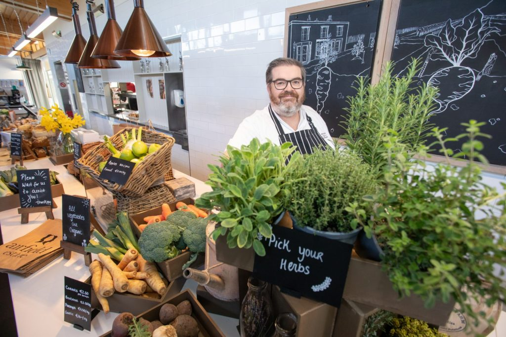 Airfield Farm Shop Photography with chef in apron with fresh produce